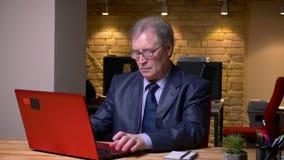 Πορτρέτο του ανώτερου ατόμου στην επίσημη δακτυλογράφηση κοστουμιών στο lap-top στην αρχή απόθεμα βίντεο