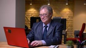 Πορτρέτο του ανώτερου ατόμου στην επίσημη δακτυλογράφηση κοστουμιών στο lap-top που είναι χαρούμενος και θετικός στην αρχή απόθεμα βίντεο