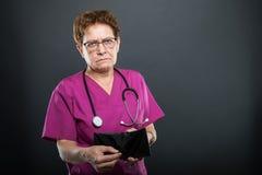 Πορτρέτο του ανώτερου γυναικείου γιατρού που παρουσιάζει κενό πορτοφόλι Στοκ Εικόνες