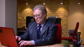 Πορτρέτο του ανώτερου επιχειρηματία στην επίσημη δακτυλογράφηση κοστουμιών στο lap-top που είναι προσεκτικές στροφές στη κάμερα κ απόθεμα βίντεο