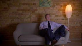 Πορτρέτο του ανώτερου επιχειρηματία στις ψύχρες κοστουμιών έξω μπροστά από τη TV μετά από τη σκληρή εργάσιμη ημέρα φιλμ μικρού μήκους