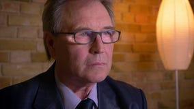 Πορτρέτο του ανώτερου επιχειρηματία στο κοστούμι και των γυαλιών που προσέχουν τις ειδήσεις στη TV που είναι σοβαρή και προσεκτικ απόθεμα βίντεο