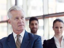 Πορτρέτο του ανώτερου επιχειρηματία ως ηγέτη με το προσωπικό στο backgrou Στοκ Εικόνα