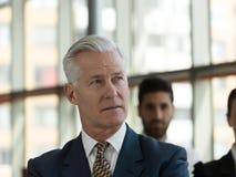 Πορτρέτο του ανώτερου επιχειρηματία ως ηγέτη με το προσωπικό στο backgrou Στοκ Φωτογραφία