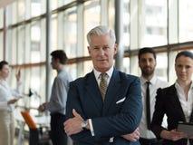 Πορτρέτο του ανώτερου επιχειρηματία ως ηγέτη με το προσωπικό στο backgrou Στοκ Εικόνες