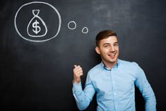 Πορτρέτο του απασχολημένου ατόμου που δείχνει στο μυαλό του για τα χρήματα στοκ φωτογραφία
