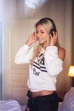 Πορτρέτο του αρκετά ευτυχούς κοριτσιού με τα ακουστικά που ακούει τη μουσική ροκ Στοκ Φωτογραφίες