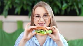 Πορτρέτο του αρκετά εφηβικού χαμόγελου γυναικών που θέτει νόστιμο ορεκτικό burger εκμετάλλευσης που εξετάζει τη κάμερα φιλμ μικρού μήκους