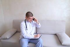 Πορτρέτο του αρμόδιου αρσενικού γιατρού που επικοινωνεί στο κύτταρο και Στοκ εικόνα με δικαίωμα ελεύθερης χρήσης
