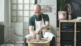 Πορτρέτο του αρσενικού επαγγελματία, ο οποίος κάνει loam το δοχείο στο φωτεινό στούντιο φιλμ μικρού μήκους