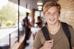 Πορτρέτο του αρσενικού εφηβικού σπουδαστή στο κολλέγιο με τους φίλους στοκ εικόνες