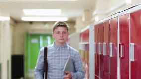 Πορτρέτο του αρσενικού περπατήματος σπουδαστών γυμνασίου κάτω από το διάδρομο και του χαμόγελου στη κάμερα απόθεμα βίντεο