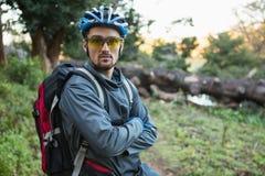 Πορτρέτο του αρσενικού ποδηλάτη βουνών με τα όπλα που διασχίζονται στο δάσος Στοκ Εικόνα