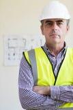 Πορτρέτο του αρχιτέκτονα που φορά το σκληρό καπέλο με τα σχέδια στο υπόβαθρο Στοκ Φωτογραφία
