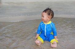 Πορτρέτο του ασιατικού αγοράκι στη συνεδρίαση κοστουμιών κολύμβησης στην παραλία άμμου στοκ εικόνα με δικαίωμα ελεύθερης χρήσης