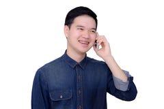 Πορτρέτο του ασιατικού ατόμου που φορά το πουκάμισο τζιν με το τηλέφωνο. Στοκ Εικόνες