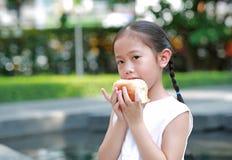 Πορτρέτο του ασιατικού μικρού κοριτσιού που τρώει το ψωμί με το γεμισμένο φράουλα-γεμισμένο επιδόρπιο στον κήπο υπαίθριο στοκ εικόνες