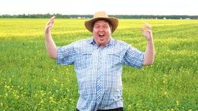 Πορτρέτο του αστείου αγρότη Άτομο που πηγαίνει τρελλό Αύξηση των χεριών και της κραυγής της Να θέσει επάνω στον τομέα την ηλιόλου απόθεμα βίντεο