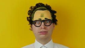 Πορτρέτο του αστείου και τονισμένου σγουρού ατόμου, τρελλός και χαρωπά της συγκίνησης, στο κίτρινο υπόβαθρο τοίχων φιλμ μικρού μήκους