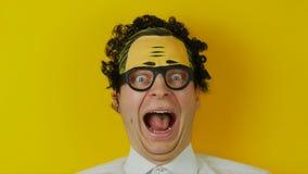 Πορτρέτο του αστείου σγουρού τύπου κραυγής, θετική τρελλή ανθρώπινη συγκίνηση, στο κίτρινο υπόβαθρο τοίχων απόθεμα βίντεο