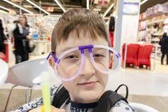 Πορτρέτο του αστείου χαριτωμένου αγοριού που φορά τα παράξενα γυαλιά φιαγμένο από φθορισμού σωλήνες νέου, λεωφόρος αγορών στοκ φωτογραφία
