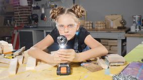 Πορτρέτο του αστείου 10χρονου κοριτσιού στην ξύλινη ξυλουργική που κρατά ένα ηλεκτρονικό τρυπάνι, που θέτει στη κάμερα οικοδόμος  απόθεμα βίντεο