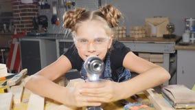Πορτρέτο του αστείου 10χρονου κοριτσιού στην ξύλινη ξυλουργική που κρατά ένα ηλεκτρονικό τρυπάνι, που θέτει στη κάμερα οικοδόμος  φιλμ μικρού μήκους