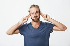 Πορτρέτο του αστείου όμορφου ατόμου με τη γενειάδα που κάνει τα ανόητα πρόσωπα και που με τα χέρια για να προσελκύσει την προσοχή Στοκ Εικόνες