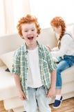 Πορτρέτο του λατρευτού μικρού παιδιού που γελά ενώ λίγη αδελφή που παίζει στον καναπέ στοκ φωτογραφία