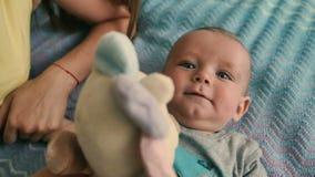 Πορτρέτο του λατρευτού μπλε-eyed μωρού στα παιχνίδια κρεβατιών με το παιχνίδι φιλμ μικρού μήκους