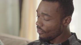 Πορτρέτο του ατόμου αφροαμερικάνων που τρώει τα πρόχειρα φαγητά και που πίνει την μπύρα με τους φίλους στο σπίτι Ελεύθερος χρόνος απόθεμα βίντεο
