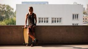 Πορτρέτο του ατόμου που στέκεται με ένα longboard και που κοιτάζει μακριά Στοκ Φωτογραφίες