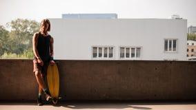 Πορτρέτο του ατόμου που στέκεται με ένα longboard Στοκ Φωτογραφίες