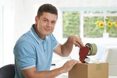 Πορτρέτο του ατόμου που σφραγίζει στο σπίτι το κιβώτιο για την αποστολή Στοκ φωτογραφία με δικαίωμα ελεύθερης χρήσης