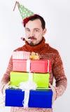 Πορτρέτο του ατόμου στις διακοπές στο καπέλο και το συριγμό με τα δώρα Στοκ Εικόνες