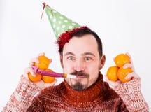 Πορτρέτο του ατόμου στις διακοπές στο καπέλο και το συριγμό με tangerines Στοκ Εικόνες