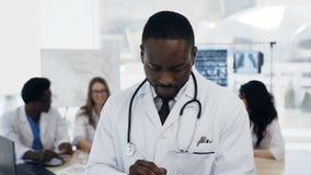 Πορτρέτο του αφρικανικού νέου αρσενικού γιατρού με την ομάδα του cowoker στο υπόβαθρο στο νοσοκομείο απόθεμα βίντεο