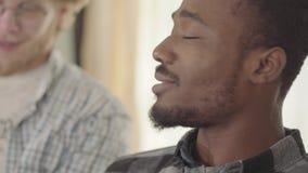 Πορτρέτο του βέβαιου ατόμου αφροαμερικάνων που τρώει τα πρόχειρα φαγητά και που πίνει την μπύρα με τους φίλους στο σπίτι Ελεύθερο απόθεμα βίντεο