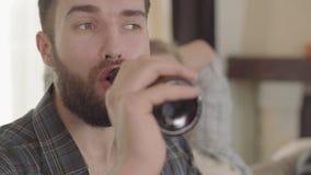 Πορτρέτο του βέβαιου ατόμου που τρώει τα πρόχειρα φαγητά και που πίνει την μπύρα με τους φίλους στο σπίτι Γενειοφόρο άτομο που απ απόθεμα βίντεο