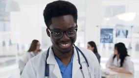 Πορτρέτο του βέβαιου αφρικανικού αρσενικού γιατρού ενώ ομάδα του cowoker που εργάζεται στο υπόβαθρο στο νοσοκομείο φιλμ μικρού μήκους