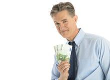 Πορτρέτο του βέβαιου επιχειρηματία που παρουσιάζει ευρο- τραπεζογραμμάτια Στοκ φωτογραφίες με δικαίωμα ελεύθερης χρήσης