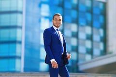 Πορτρέτο του βέβαιου εύθυμου επιχειρηματία στην μπλε στάση κοστουμιών στοκ εικόνα με δικαίωμα ελεύθερης χρήσης