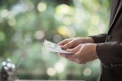 Πορτρέτο του βέβαιου νέου ασιατικού κοιτάγματος επιχειρηματιών στη δεξιά πλευρά Δίνει τα μετρώντας τραπεζογραμμάτια δολαρίων, Στοκ φωτογραφία με δικαίωμα ελεύθερης χρήσης