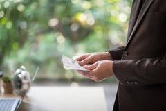 Πορτρέτο του βέβαιου νέου ασιατικού κοιτάγματος επιχειρηματιών στη δεξιά πλευρά Δίνει τα μετρώντας τραπεζογραμμάτια δολαρίων, Στοκ Εικόνες