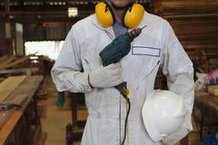 Πορτρέτο του βέβαιου νέου ξυλουργού με ηλεκτρικό τρυπάνι εκμετάλλευσης ασφάλειας το ομοιόμορφο στο εργοστάσιο εργαστηρίων ξυλουργ στοκ φωτογραφίες