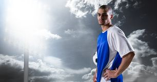 Πορτρέτο του βέβαιου ποδοσφαιριστή με το χέρι στο ισχίο ενάντια στον ουρανό Στοκ Εικόνα