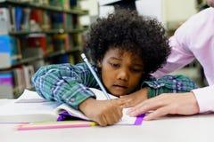 Πορτρέτο του βοηθώντας μικρού παιδιού δασκάλων με την εργασία στο λι στοκ εικόνες