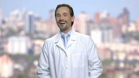 Πορτρέτο του γελώντας ώριμου ατόμου στο άσπρο παλτό φιλμ μικρού μήκους