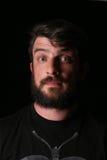 Πορτρέτο του γενειοφόρου ατόμου με το ενδιαφέρον βλέμμα κλείστε Επάνω μαύρα Στοκ Εικόνες