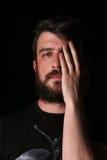 Πορτρέτο του γενειοφόρου ατόμου με το χέρι στο πρόσωπό του κλείστε Επάνω μαύρα Στοκ Εικόνες
